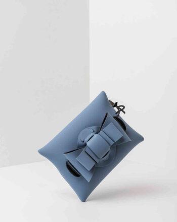 Una pochette da donna in neoprene con una zip sul retro, un fiocco con lavorazione ad intreccio ben visibile sulla patta frontale e il logo AP di colore nero, pendente, in gomma. La borsa è di colore carta da zucchero.