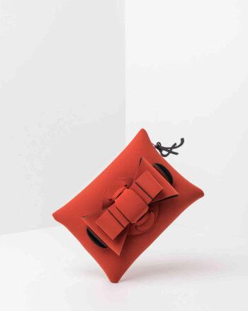 Una pochette da donna in neoprene con una zip sul retro, un fiocco con lavorazione ad intreccio ben visibile sulla patta frontale e il logo AP di colore nero, pendente, in gomma. La borsa è di colore cotto.