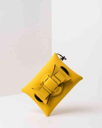 Una pochette da donna in neoprene con una zip sul retro, un fiocco con lavorazione ad intreccio ben visibile sulla patta frontale e il logo AP di colore nero, pendente, in gomma. La borsa è di colore giallo.