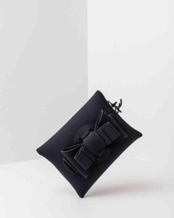 Una pochette da donna in neoprene con una zip sul retro, un fiocco con lavorazione ad intreccio ben visibile sulla patta frontale e il logo AP di colore nero, pendente, in gomma. La borsa è di colore nero.