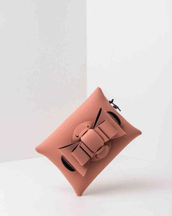 Una pochette da donna in neoprene con una zip sul retro, un fiocco con lavorazione ad intreccio ben visibile sulla patta frontale e il logo AP di colore nero, pendente, in gomma. La borsa è di colore rosa pig.