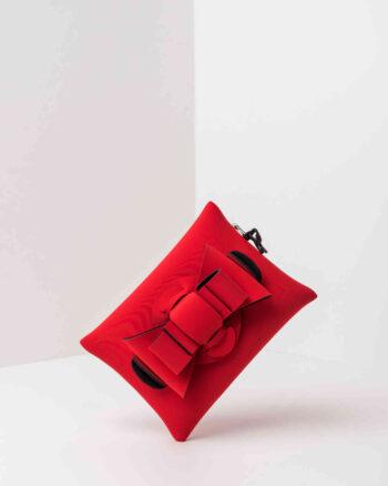 Una pochette da donna in neoprene con una zip sul retro, un fiocco con lavorazione ad intreccio ben visibile sulla patta frontale e il logo AP di colore nero, pendente, in gomma. La borsa è di colore rosso.