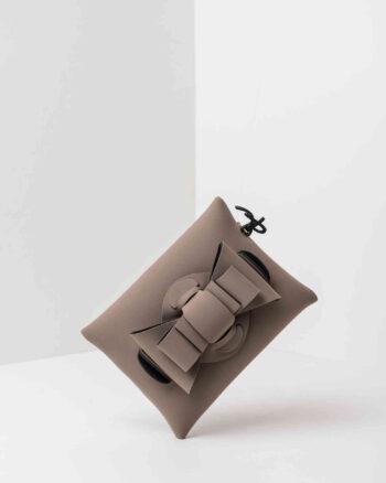 Una pochette da donna in neoprene con una zip sul retro, un fiocco con lavorazione ad intreccio ben visibile sulla patta frontale e il logo AP di colore nero, pendente, in gomma. La borsa è di colore taupe.