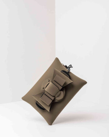 Una pochette da donna in neoprene con una zip sul retro, un fiocco con lavorazione ad intreccio ben visibile sulla patta frontale e il logo AP di colore nero, pendente, in gomma. La borsa è di colore verde militare.