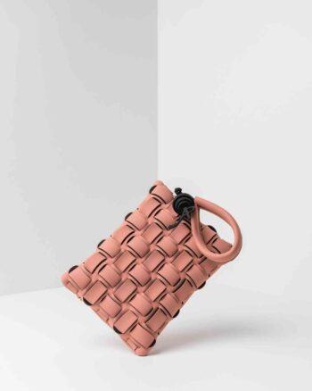 Una pochette da donna in neoprene lavorata ad intreccio sulla parte frontale, con chiusura a zip sul retroo, un anello per indossarla al polso. Logo AP in gomma di colore nero, come accessorio pendente. La borsa è di colore rosa pig.
