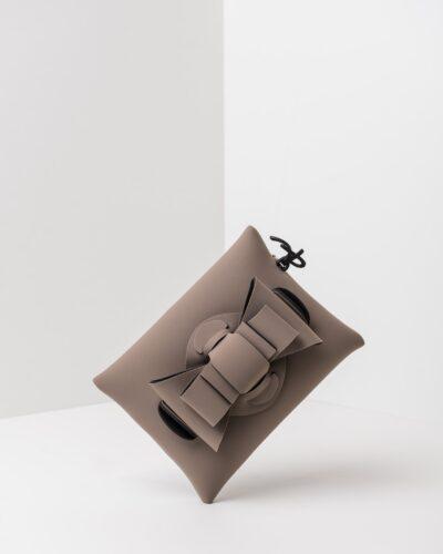 La foto ritrae una borsa modello pochette della linea Chérie di APbag. Si tratta di una borsa lavabile effetto neoprene, disegnata da Stefano Galandrini, prodotta e distribuita da Artpelle.it La borsa è di colore taupe.