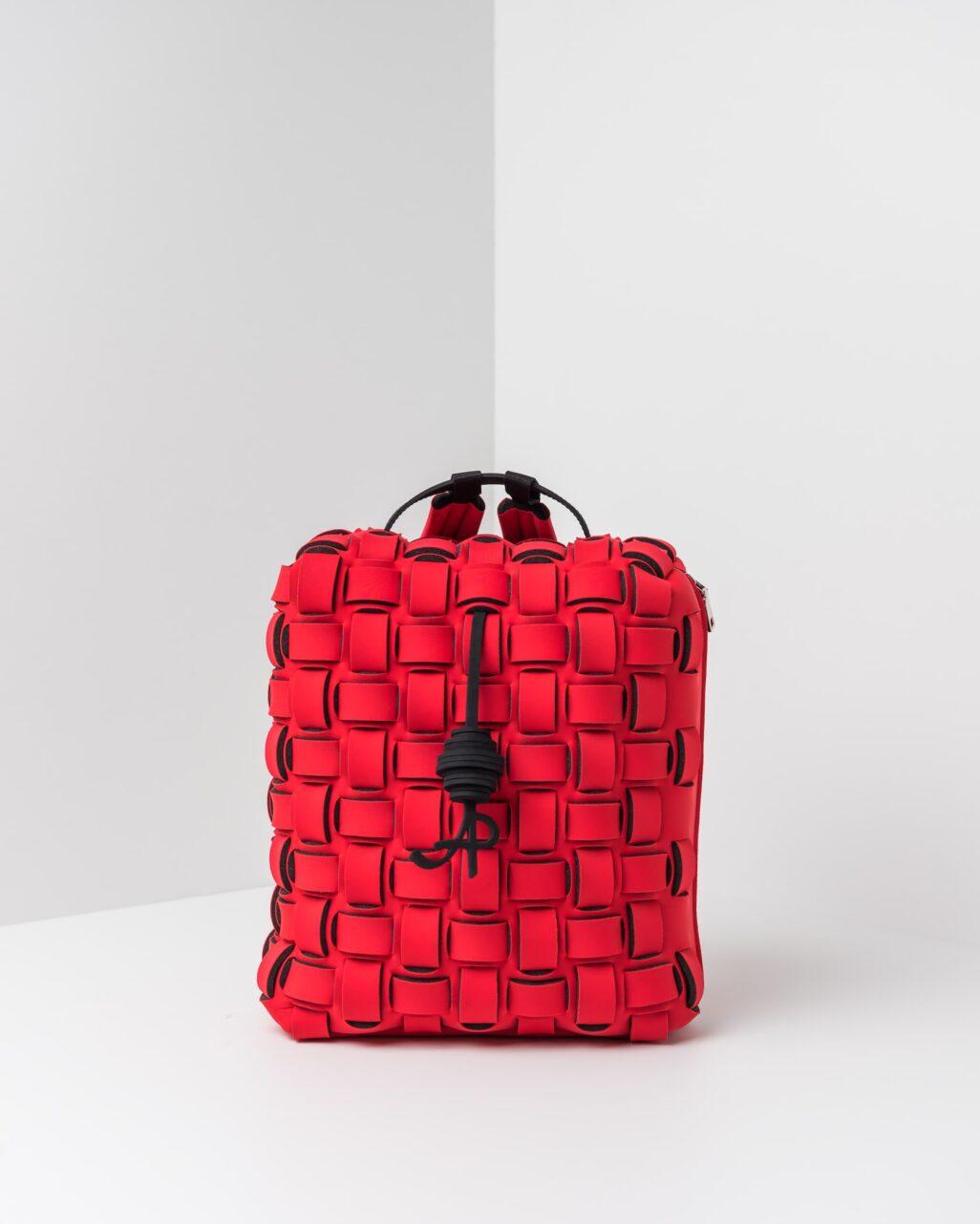 La foto ritrae uno zaino con lavorazione a trama intrecciata della linea Madison di APbag. Si tratta di una borsa lavabile effetto neoprene disegnata da Stefano Galandrini, prodotta e distribuita da Artpelle.it Lo zaino è di colore rosso.